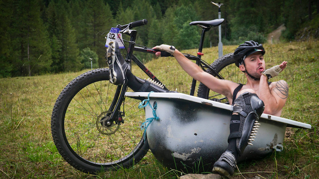 Cyclist sitting inside a bathtub in grass, hold up a black Surly bike with trees in the background