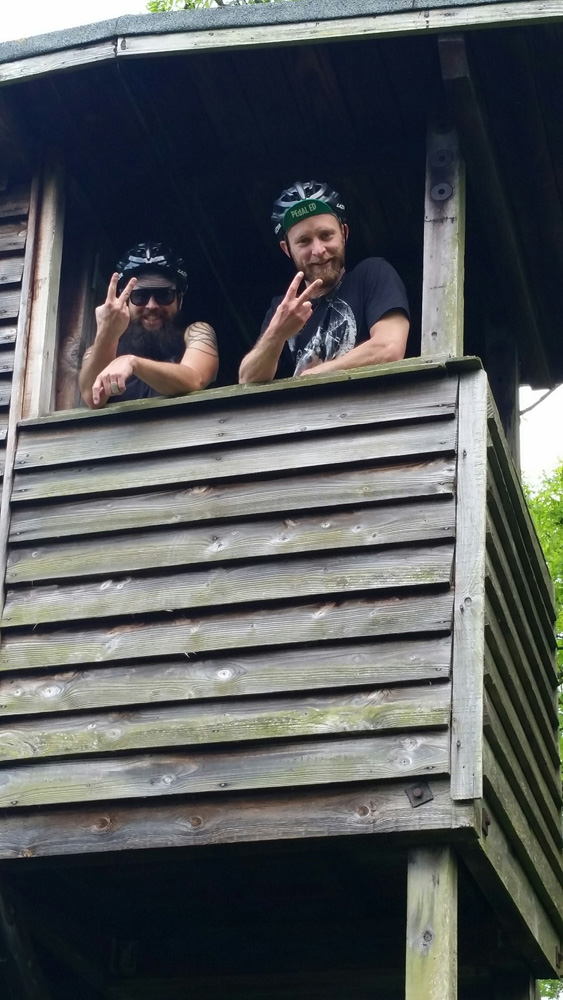 Two people standing next to each holding 2 finger up while in an opening of a wood building on stilts