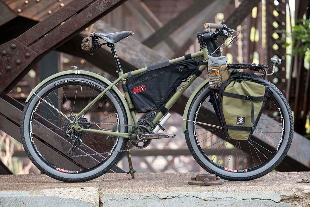 Right side profile of olive green Surly Bridge club bike with front saddle bag on a concrete slab of a steel bridge