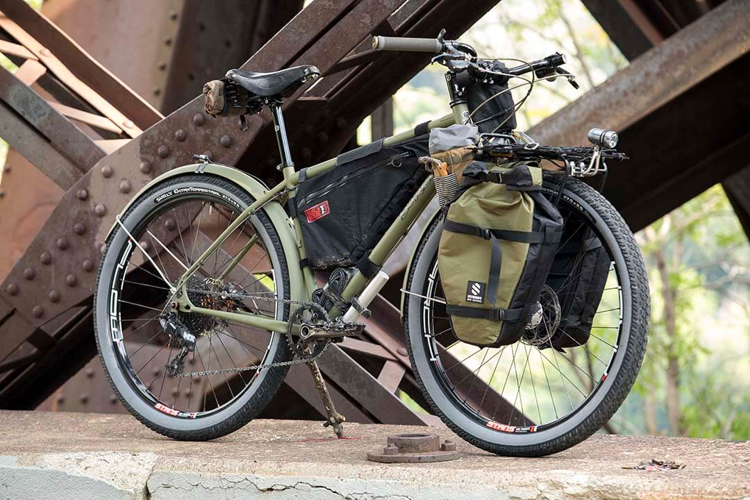 Front angled right profile of olive green Surly Bridge Club bike with front saddle bag on a rusty steel bridge