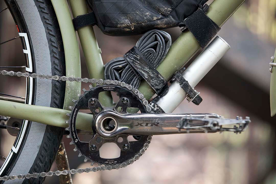 Right side close up of silver crankset, chain, portion of the back wheel of an olive green Surly Bridge Club bike