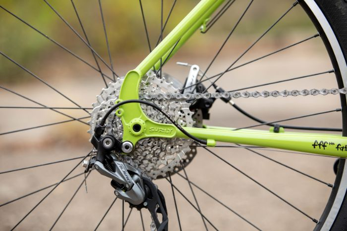 Zoom in of the back portion of a Surly Disc Trucker bike focused on rear derailleur - cassette -pulley wheels