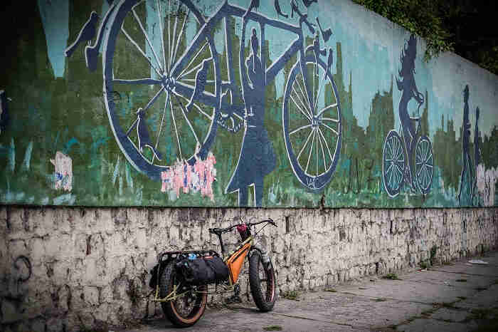 Rear right side view of a Surly Big Fat Dummy bike on a sidewalk, against a wall with a mural