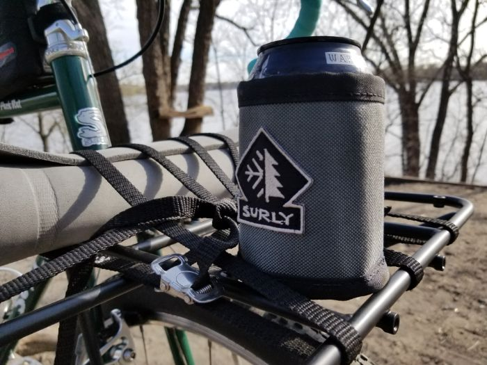 Zoom in of a can in a Surly can cooler mounted to the front rack of a bike with trees and lake in the background