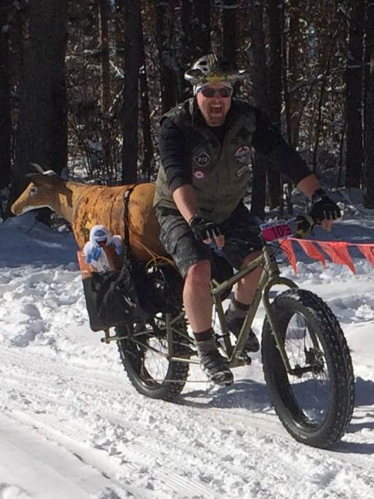 Front view of a cyclist riding a Surly Big Fat Dummy bike on a snowy trail with trees in the background