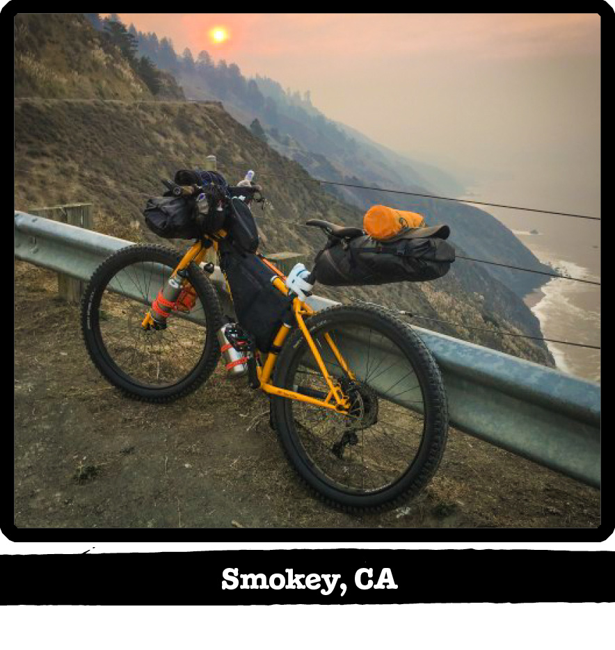 Left side view of a Surly bike leaning on a roadside guardrail on a cliff over the coast-Smokey, CA banner below image