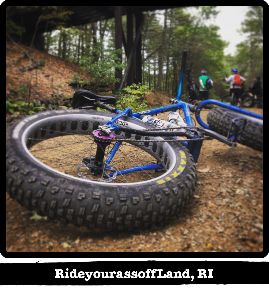 Rear view of a Surly fat bike laying on the left side in gravel, in the woods-RideyourassoffLand, RI banner below image