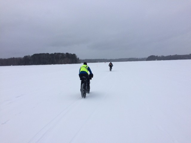 Rear view of 2 cyclists riding their fat bikes across a frozen, snow covered lake