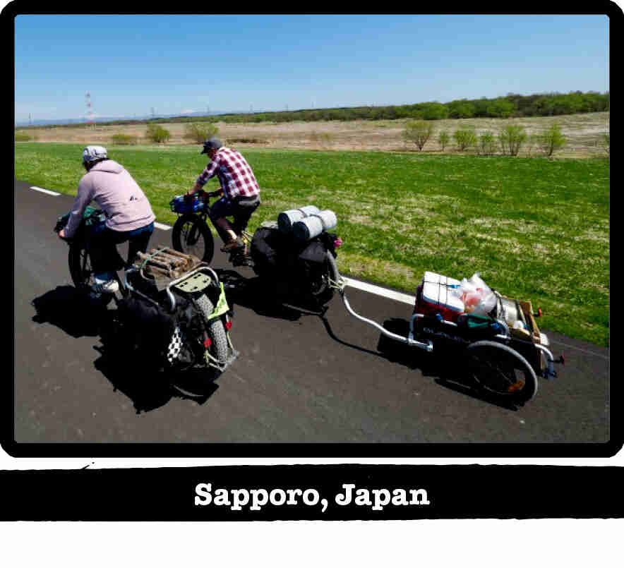 Rear view of 2 cyclists riding Surly fat bikes on a remote paved road - Sapporo, Japan tag below image