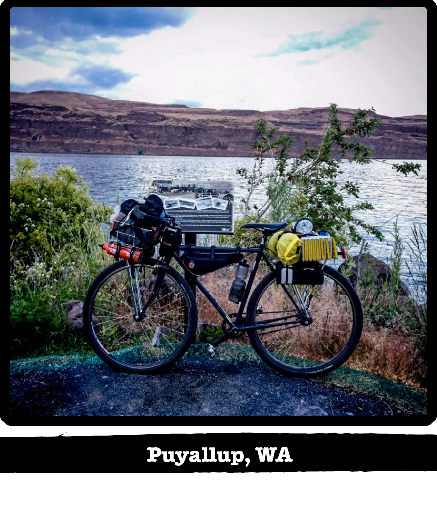Left side view of Surly bike with gear, leaning on a post with a lake and hills behind-Puyallup, WA banner below image