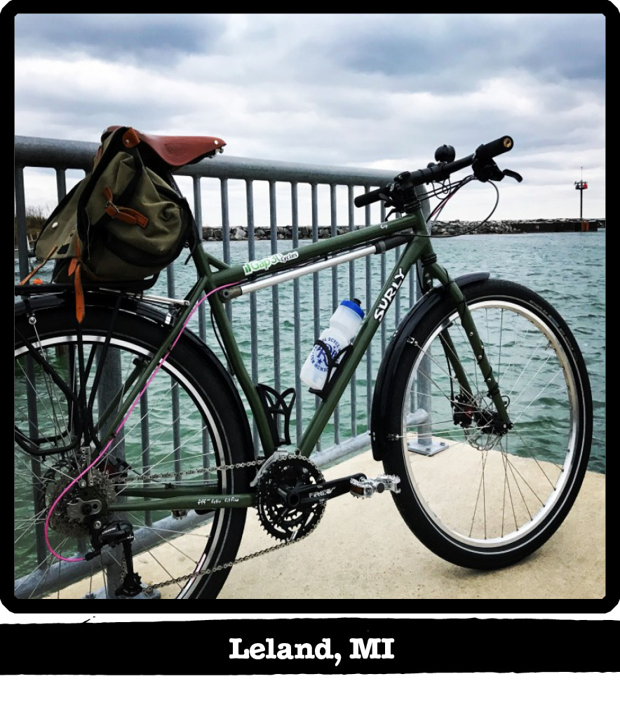 Right side view of a green Surly bike against a rail on a dock facing a waterway-Leland, MI banner shown below image