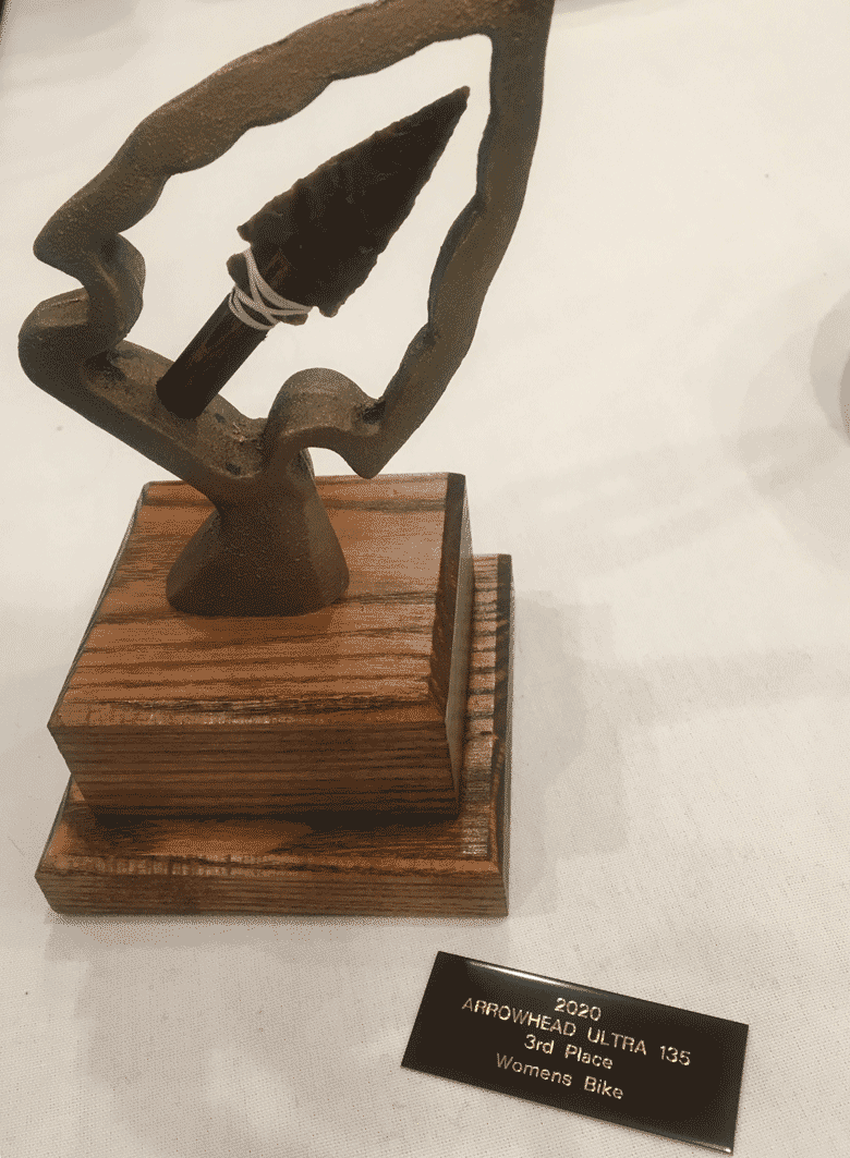 Downward view of Trophy with arrowhead on wood base with an Arrowhead Ultra 135 third place plague next to it on a table