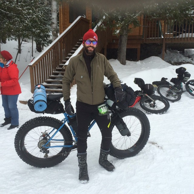 Front view of a cyclist, with their fat bike behind them, standing in snow with a cabin in the background