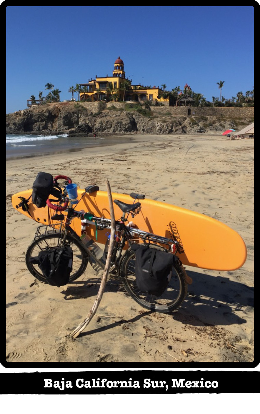 Left side view of a bike, gear and surfboard mounted, on the beach-Baja California Sur, Mexico banner below image
