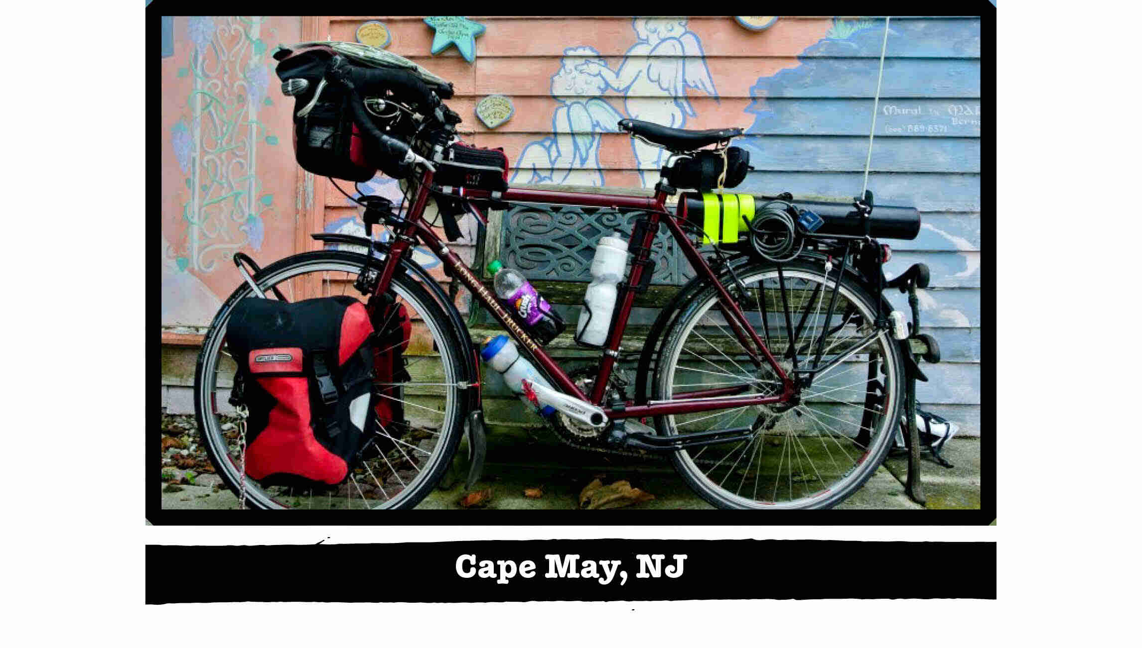 Left side view of a Surly Trucker bike, loaded with gear, in front of a wall with a mural - Cape May, NJ tag below image