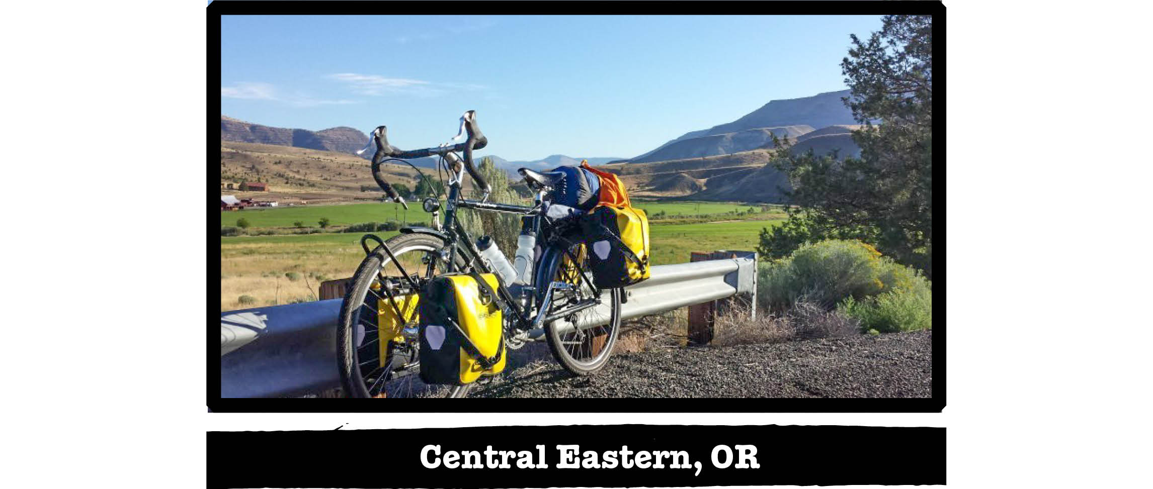 Left side view of a Surly Long Haul Trucker bike, along a rail with hills behind - Central Eastern, OR tag below image