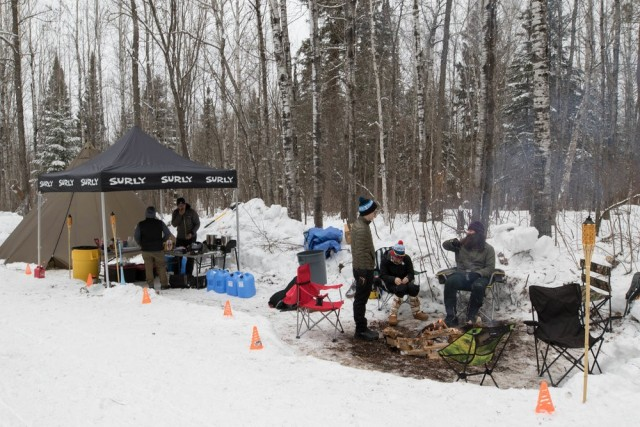 People gather around a snowy campsite with a Surly canopy, and trees in the background