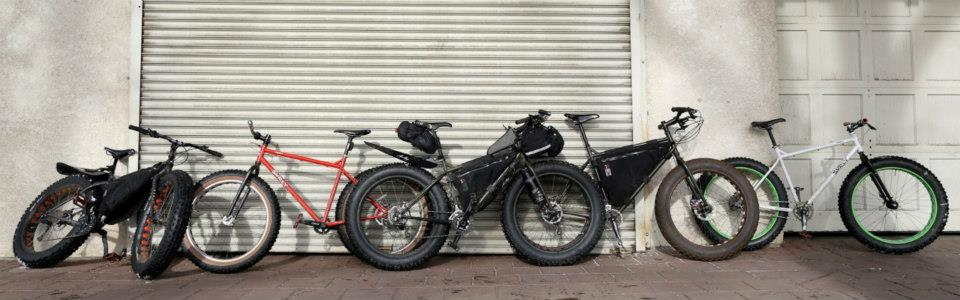 Side view of Surly fat bikes, leaning against the outside of 2 large, white, garage doors