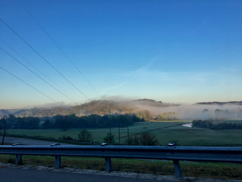 View from  a roadside guardrail with green fields, tree and fog covered hills in the distance