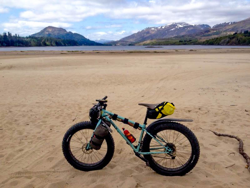 Left side view of a Surly Wednesday MY17 fat bike, in a field of sand, with a lake and mountains in the background