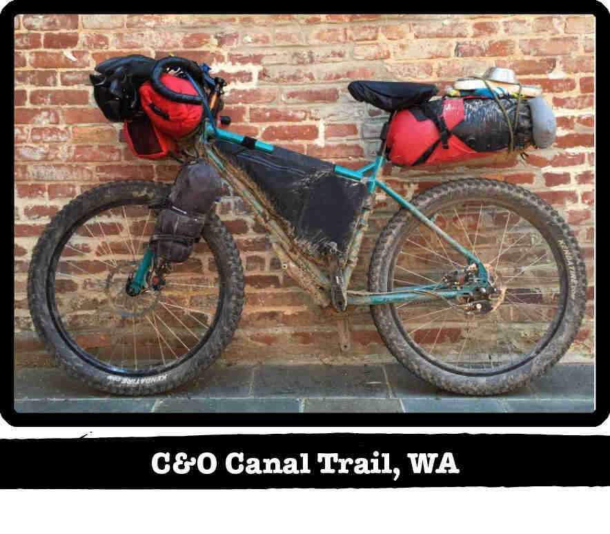 Left side view of a muddy Surly bike with gear, leaning against a red brick wall - C&O Canal Trail, WA tag below image