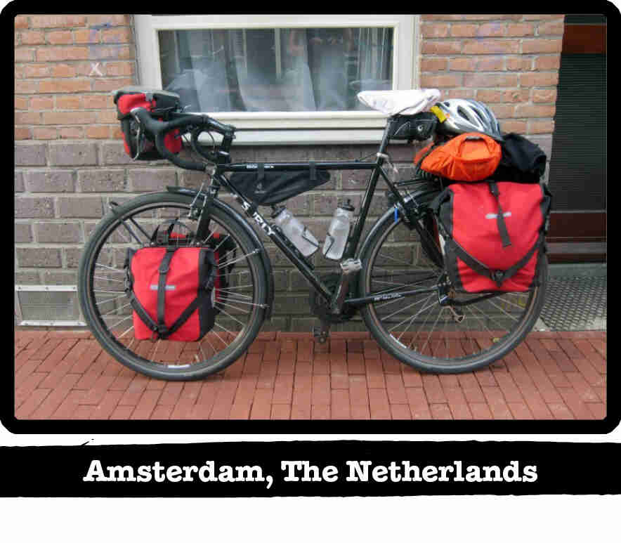 Left side view of a Surly bike loaded with gear, on a red brick sidewalk - Amsterdam, The Netherland tag below image