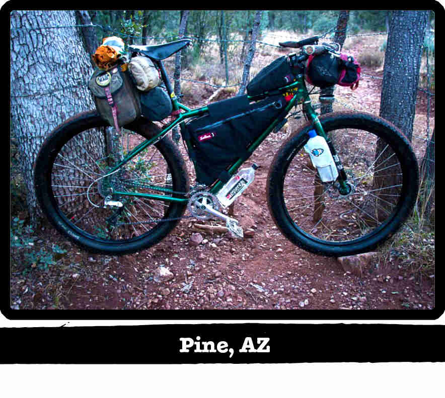 Right side view of a green Surly bike with gear, on red gravel in the woods - Pine, AZ tag below image