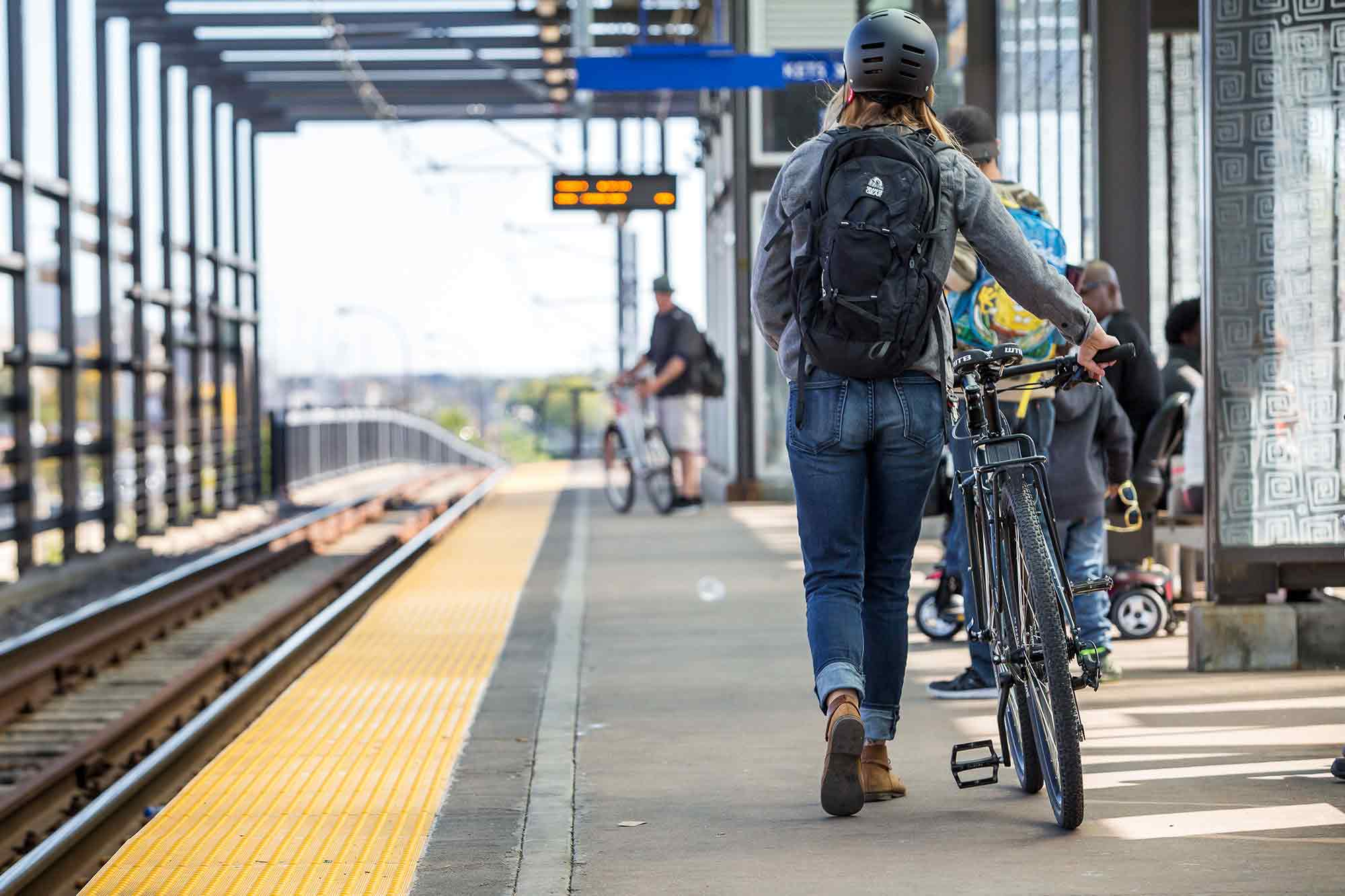 Cyclist with backpack and helmet walking bike to commuter train stop