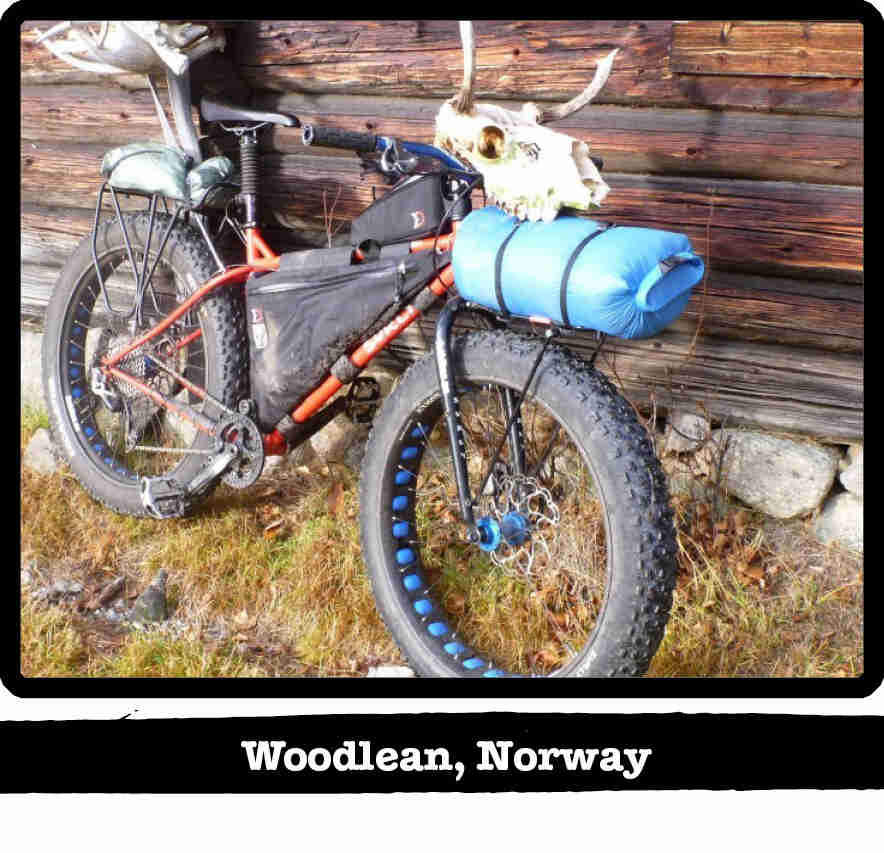 Right side view of an orange Surly fat bike with gear a a bull skull on the handle - Woodlean, Norway tag below image
