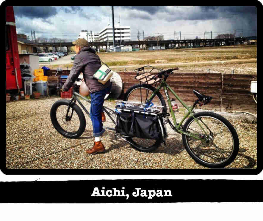 Cyclist on a Surly BIg Fat Dummy with another bike on back, with city in the background - Aichi, Japan tag below image