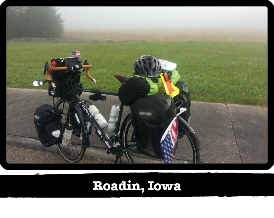 Left side view of a Surly bike loaded with gear on the side of a road, with fog behind - Roadin, Iowa tag below image