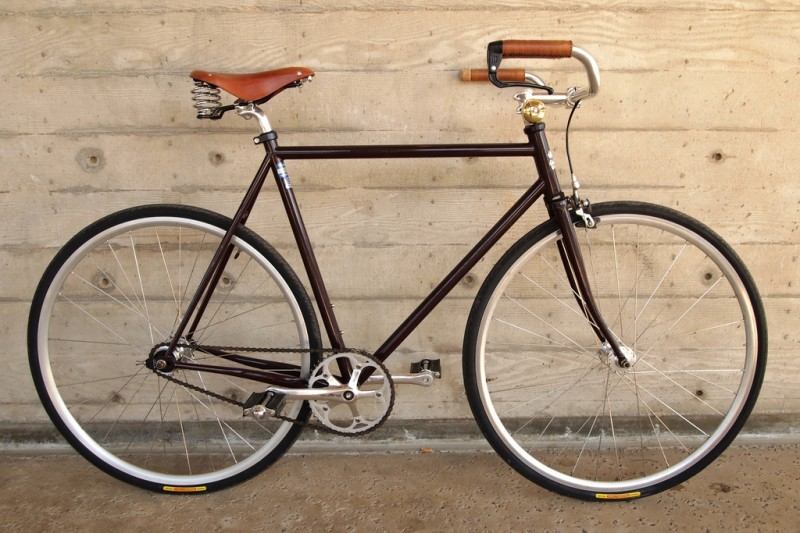 Right side view of a brown Surly bike, with a leather seat and grips, leaning against a cement wall