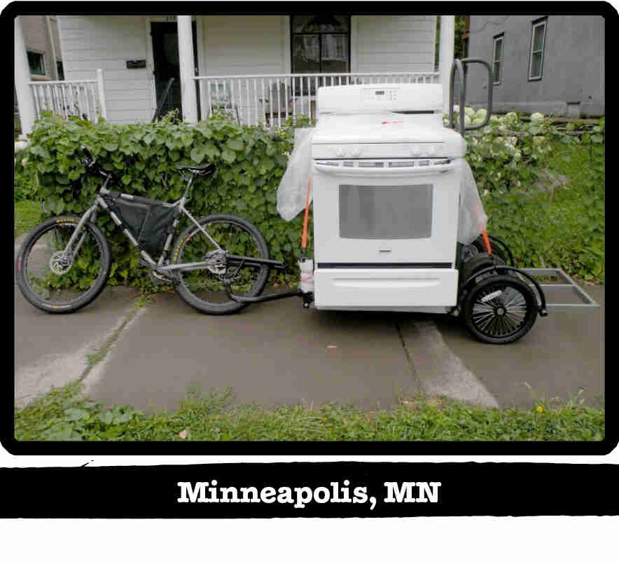 Left side view of a Surly bike pulling a stove on a trailer on a sidewalk - Minneapolis, MN tag below image