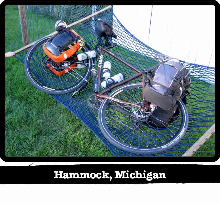 Downward left side view of a Surly bike with gear, lying in a hammock above grass - Hammock, MI tag below image