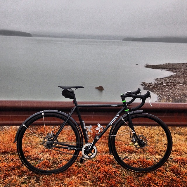 Right side view of a black Surly bike with fenders, leaning on a steel, road guardrail, with a foggy lake behind it