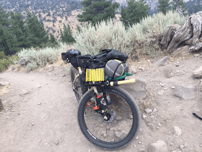 Front downward view of a Surly bike loaded with gear, on a mountain gravel trail, with brush and trees background