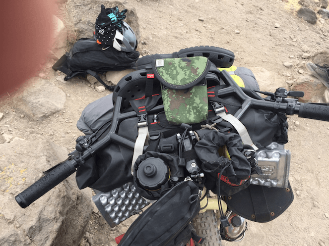 Downward view of the handlebar loaded with gear, on a bike on rocky gravel