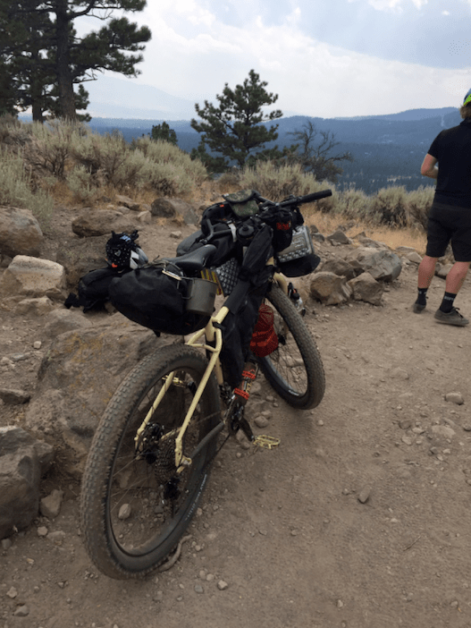 Rear view of a Surly bike loaded with gear, on a dirt mountain hill clearing, with mountains in the background