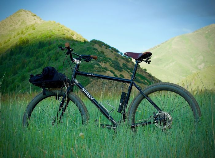 Left side view of a black Surly Bridge Club bike, standing in a field of tall green grass, with large hills behind it