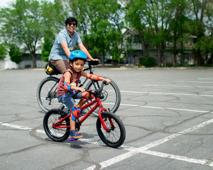 Right side view of a child on a BMX bike, in a parking lot, with a cyclist riding a Surly Bridge Club bike behind them