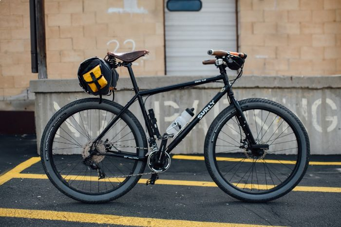 Right side view of a black Surly Bridge Club bike, parked on a pavement, in front of a loading dock on a building