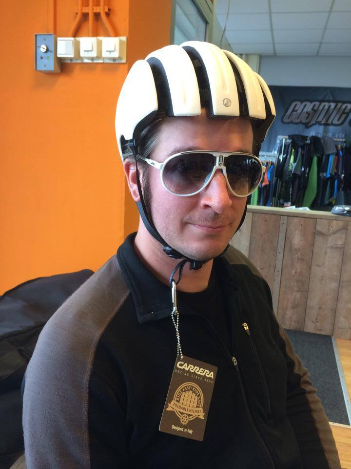 Head shot of a person wearing a bike helmet and sunglasses, with an orange wall and a counter in the background