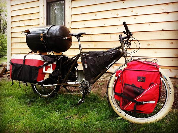 Surly BIg Easy bike loaded with gear and smaller smoker on rear rack in front of a wood sided house