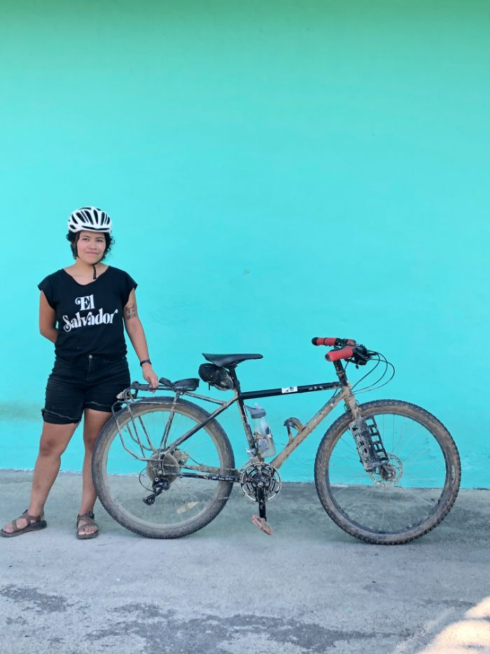 Andrea posing with her bike in front of a blue wall