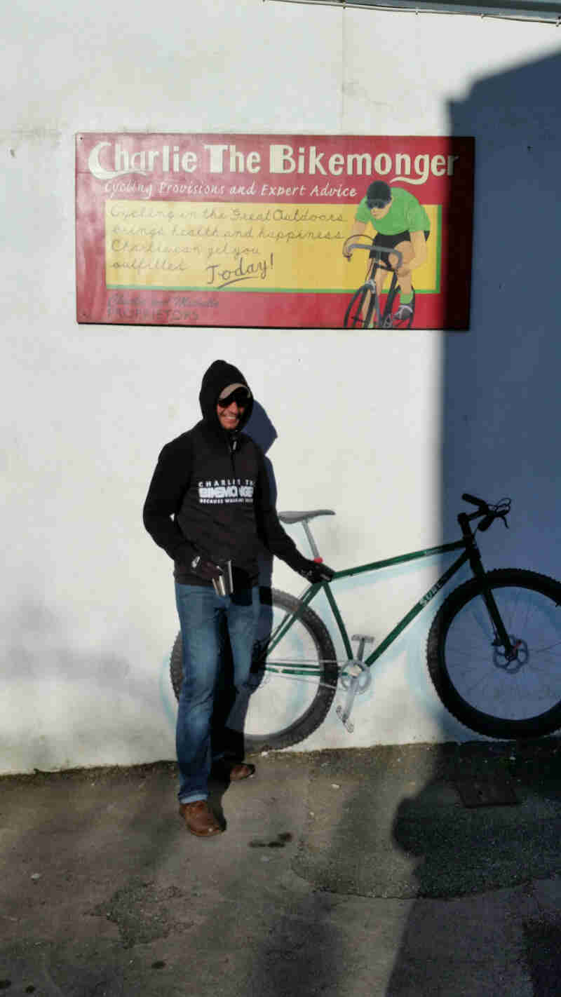 Front view of person standing against a while wall with a bike and sign painted on it