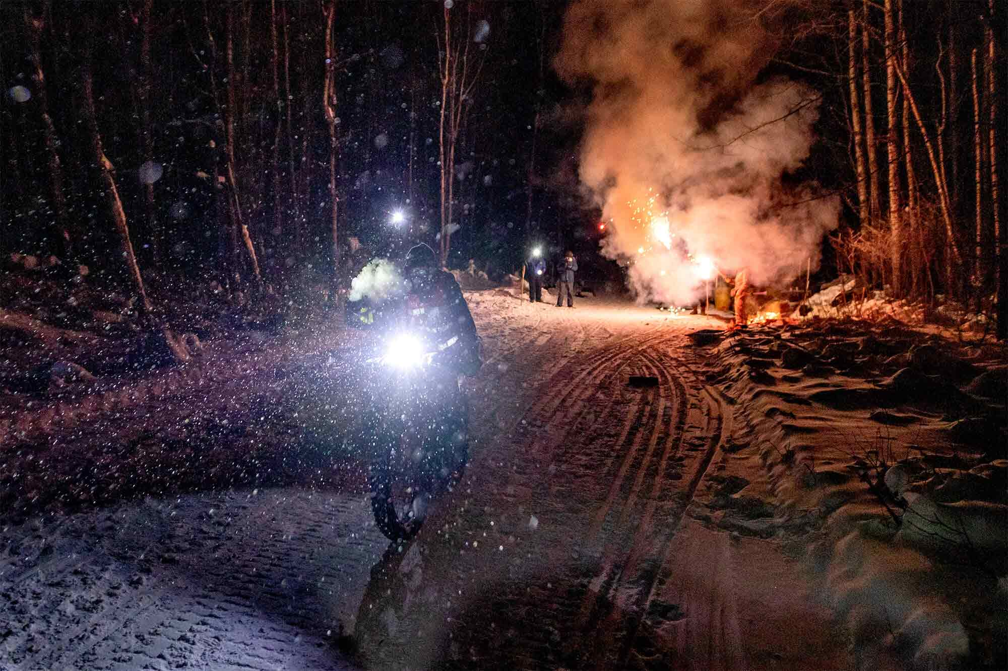 Cyclist riding a bike with a headlight, in the snow at night with fireworks exploding on the ground behind
