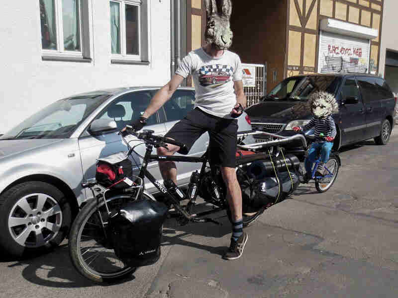 A cyclist wearing a rabbit mask, on a Surly Big Dummy bike, on a street next to a parked car - left front view