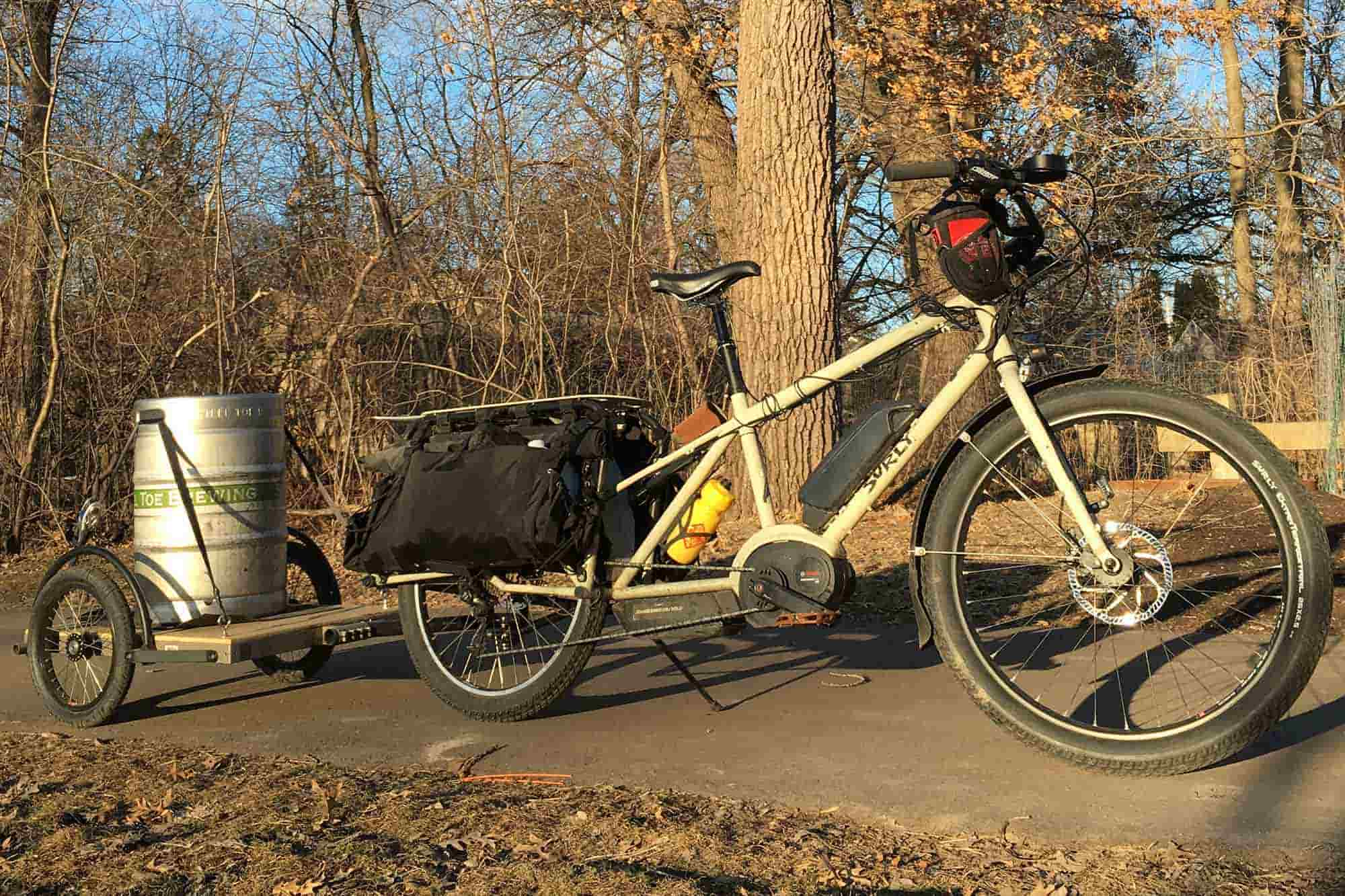 Right profile view of a tan Surly Big Easy bike with gear pulling a trailer with keg on a paved trail with trees behind