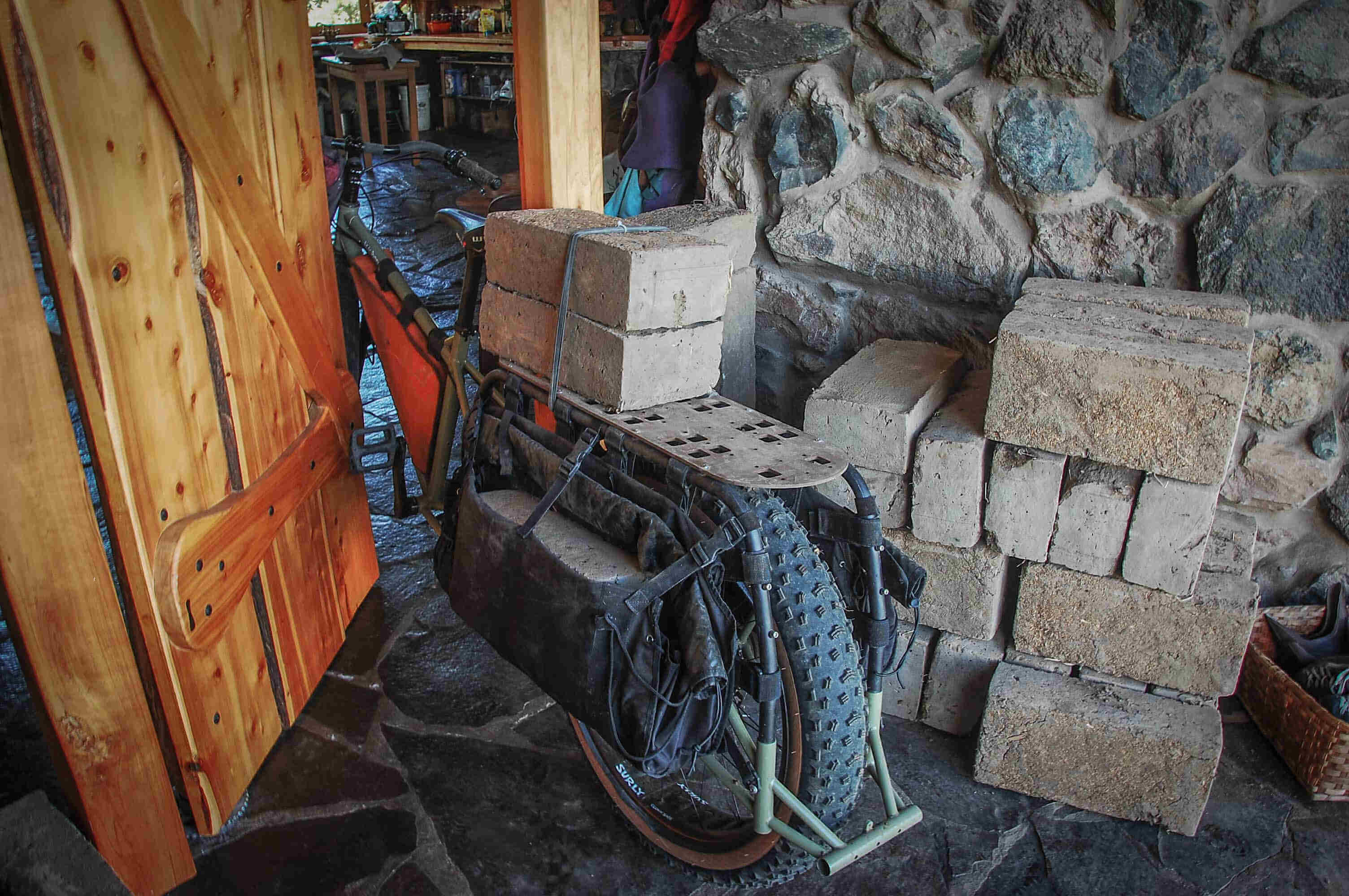 Left rear view of a Surly Big Fat Dummy bike with cement blocks on the rear rack, in the doorway of a stone building
