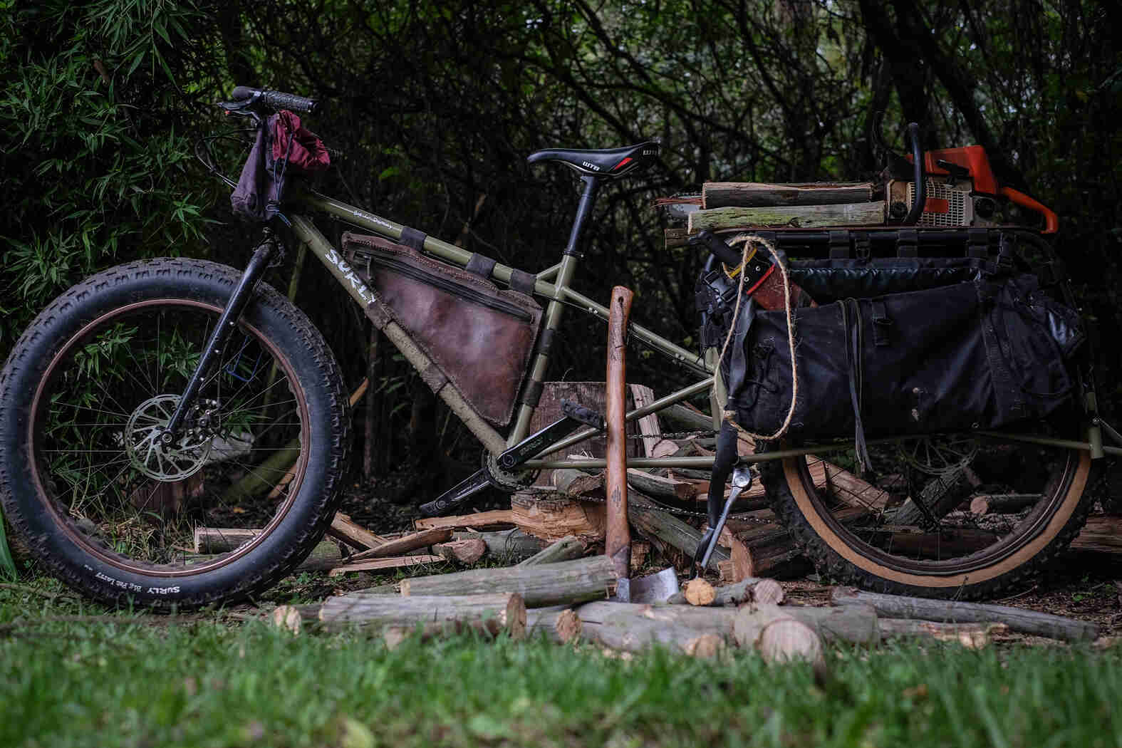 Left view of a Surly Big Fat Dummy bike, on top of axe chopped logs, with thick woods in the background